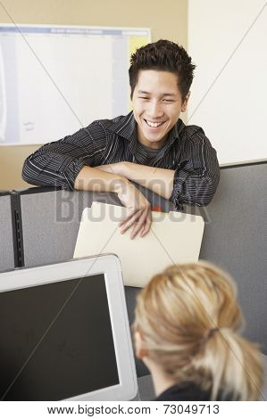 Businessman talking to colleague over cubicle wall