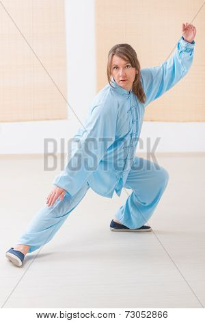 Beautiful woman doing qi gong tai chi exercise wearing professinal, oryginal chinese clothes at gym