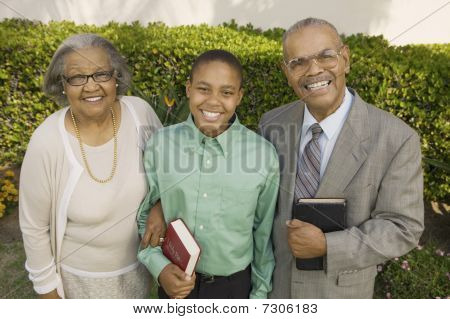 Christian Grandparents and Grandson in garden holding Bibles portrait