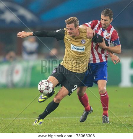 VIENNA, AUSTRIA - OCTOBER 22 Gabi (#14 Atletico) and Roman Kienast (#24 Austria) fight for the ball at a UEFA Champions League game on October 22, 2013 in Vienna, Austria.