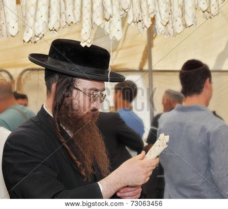 BNEI- BRAK, ISRAEL - SEPTEMBER 17, 2013: Traditional market before the holiday of Sukkot. Religious Jews in black hats and skullcap of carefully selected ritual fruits and plants