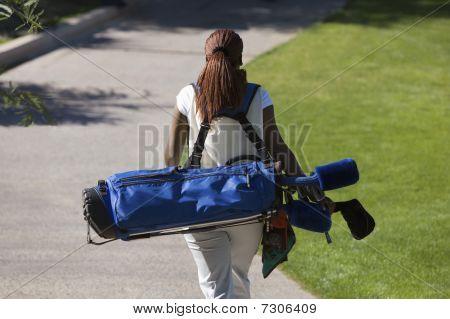 Woman carrying golf club bag rear view