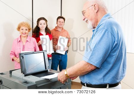 Senior man smiles as he casts his ballot on a new electronic voting machine.