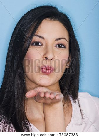 Portrait of young woman blowing a kiss