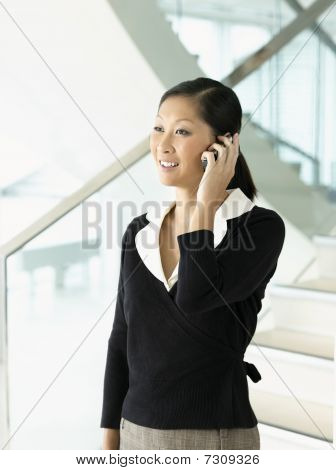 Smiling businesswoman debout parlant sur mobile