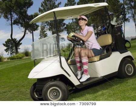 Young Female Golfer In Sitting In Cart, Smiling