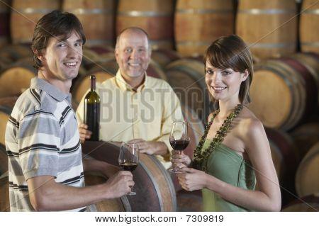 Three people wine-tasting beside wine casks portrait