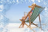 Woman in sunhat sitting on beach in deck chair using tablet pc against snow poster
