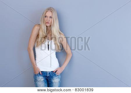 Casual nordic beauty in jeans and top posing by blue wall.
