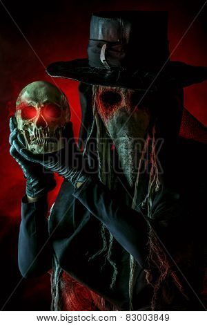 Medieval plague doctor stands with a skull. Medieval Europe. Halloween.