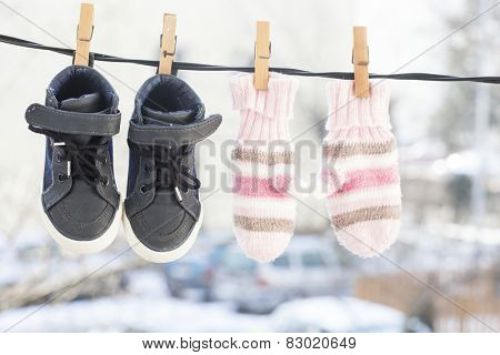 Baby clothes, gloves and shoes, hanging on the clothesline.