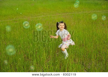 Happy Little Girl Among Soap Bubbles