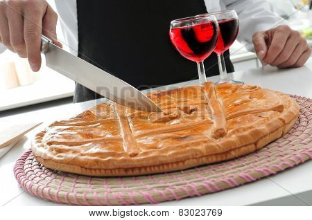 closeup of a cook who is about to cut an empanada gallega, a savory stuffed cake typical Spain, in a cooking workshop