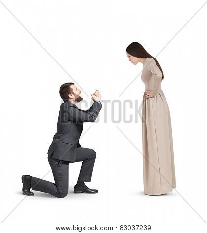 full length portrait of emotional couple isolated on white background. angry woman looking at man, man standing on knee and apologizing