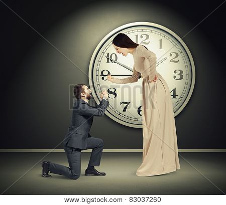 angry yelling woman and crying man in dark room with big clock on the wall