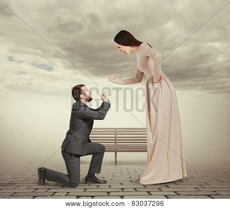 full length portrait of emotional couple in foggy park. woman screaming and showing fist, man standing on knee and apologizing