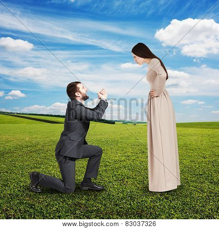 full length portrait of couple at outdoor. angry woman looking at man, man standing on knee and apologizing