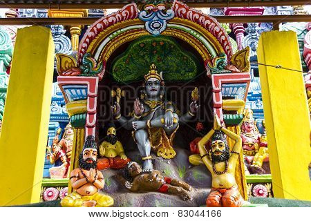 Statue of Lord Shiva called here as Dakshinamurthy sitting along with sages and dwarf demon Apasmara below his right leg as seen inside a Hindu temple poster