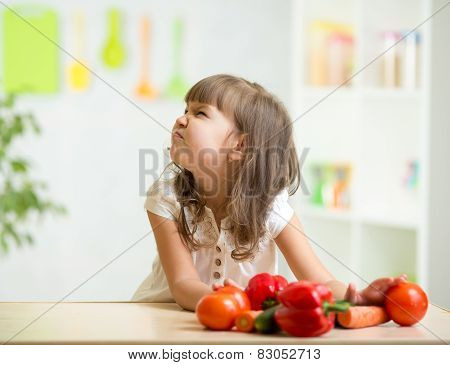 kid girl with expression of disgust against vegetables