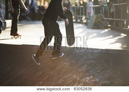 Anonymous skateboarder carrying a skateboard in a park on a sunny day
