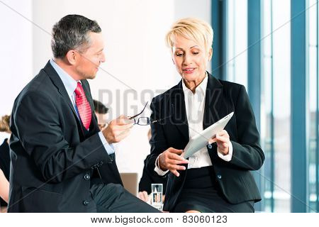Business - meeting in office, two senior managers are discussing a document on tablet computer