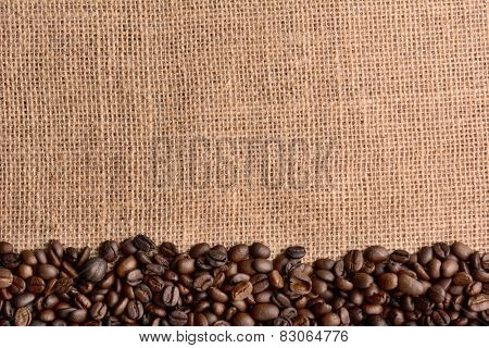 High angle horizontal shot of fresh roasted coffee beans on a burlap surface. The beans fill the bottom of the frame, the top half is open for copy space.