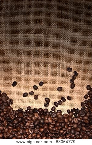 High angle shot of fresh roasted coffee beans on a light to dark burlap surface. The beans fill the bottom of the frame, the top half is open for copy space.