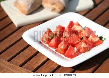 tomatoes with basil on white plate
