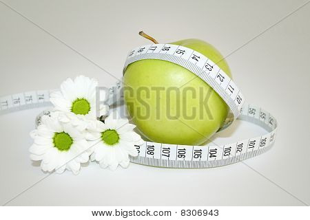 measuring tape and green apple with flowers