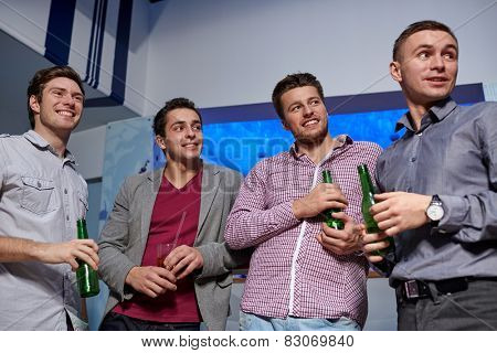 nightlife, party, friendship, leisure and people concept - group of smiling male friends with beer bottles drinking in nightclub poster