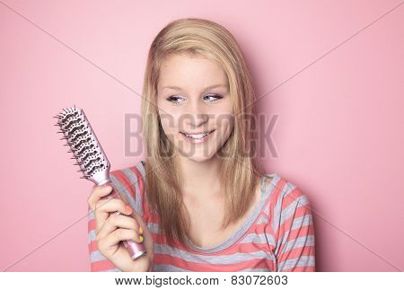 A teen who brushing her hair in her bedroom