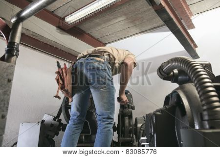 machinist worker technicians at work adjusting lift with spanners in elevator hoistway poster
