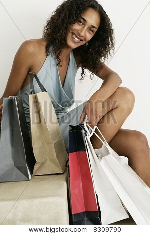 Female looking cheerful to camera with shopping bags