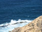The rocks and the wave breakers of the Atlantic ocean at  Punto de Paso Chico on the island Fuerteventura belonging to Spain poster