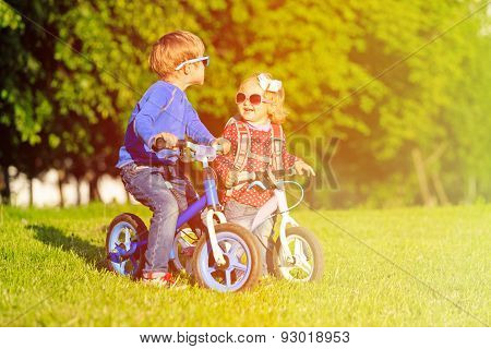 little boy and toddler girl on bikes in summer park