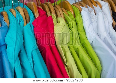 Rainproof jackets in bright colors on a rack for sale.