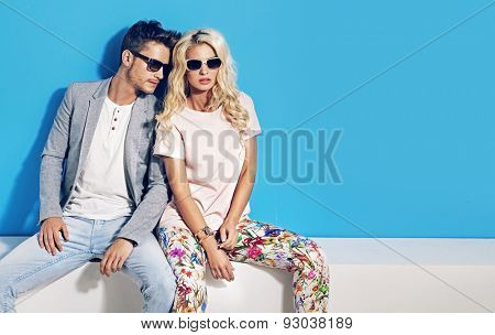 Young fashionable couple on blue background