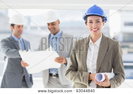 Businessmen and a woman with hard hats holding blueprint in the office