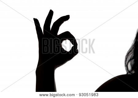 Silhouette of woman showing okey
