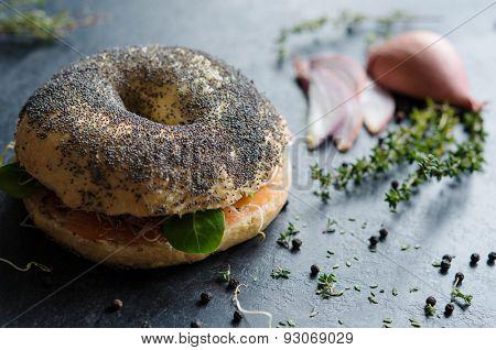 Sandwich with poppy seeds and lox on blackboard
