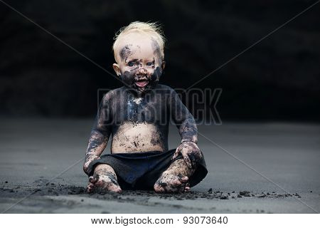 Portrait Of Dirty Child On The Black San Beach