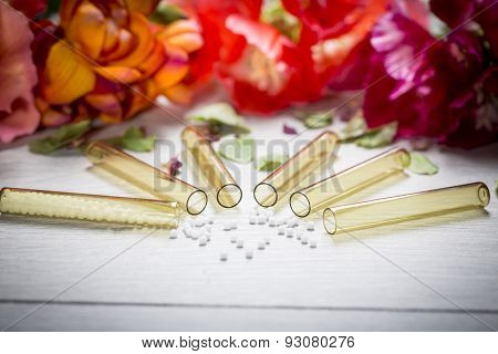 Some Small Glass Tubes With Homeopathy Globules And Flowers