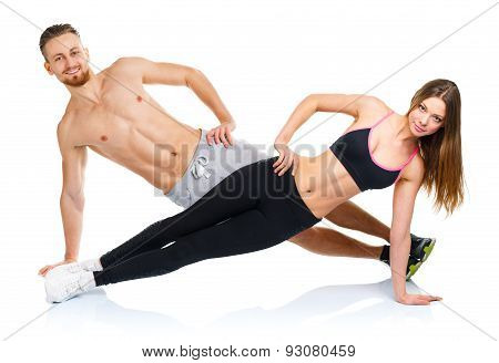 Attractive Sport Couple - Man And Woman Doing Fitness Exercises On The White