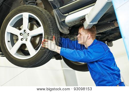 car mechanic inspecting suspension or brakes in car wheel of lifted automobile at repair service station