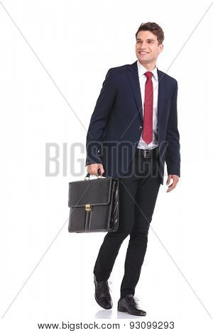 Happy young business man walking with a briefcase in his hand while looking away from the camera.