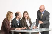 businesspartners at the table in front of a laptop poster