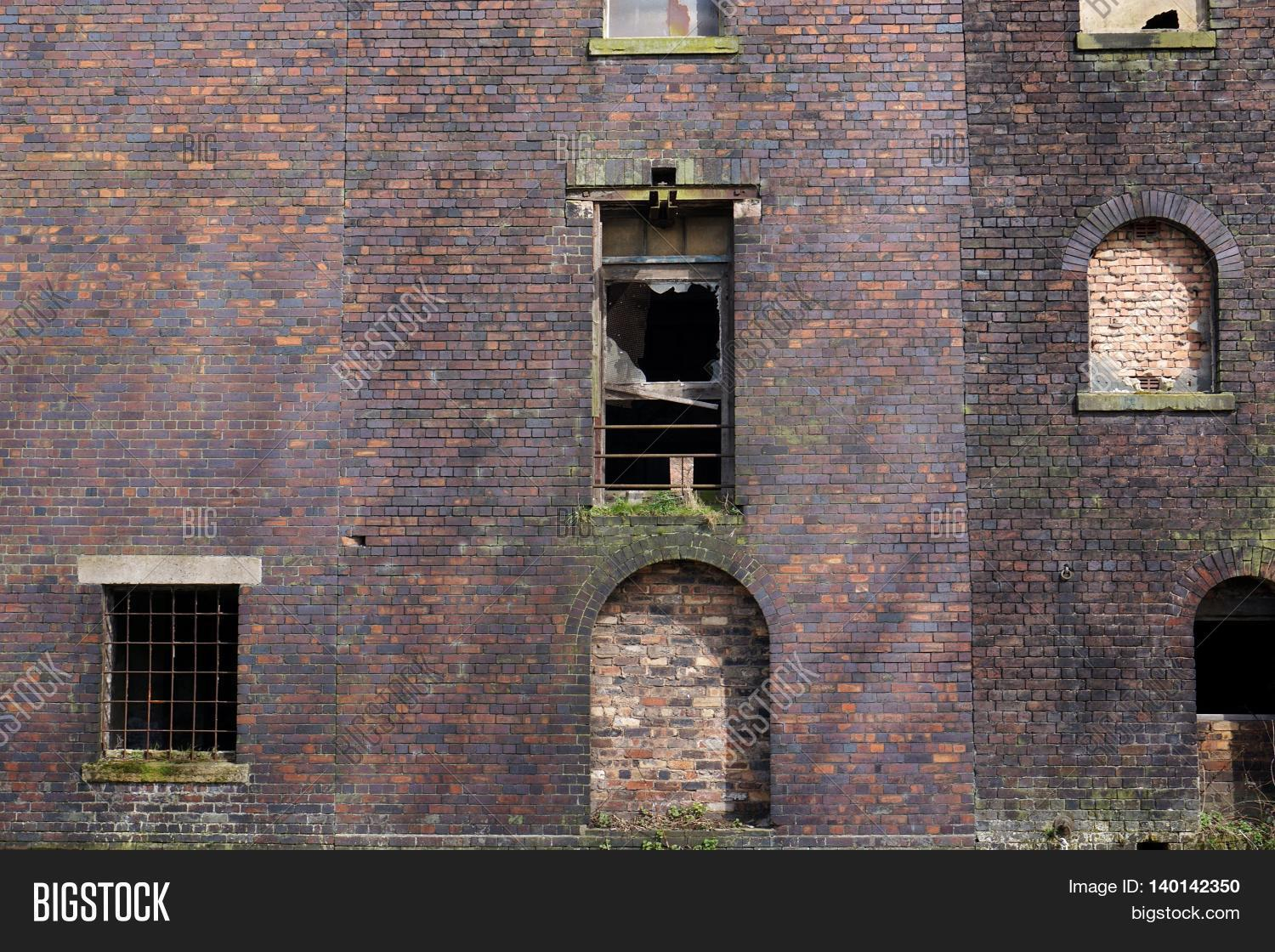 Side View Of An Abandoned Red Brick Warehouse Or Factory Building With Boarded Up And Broken
