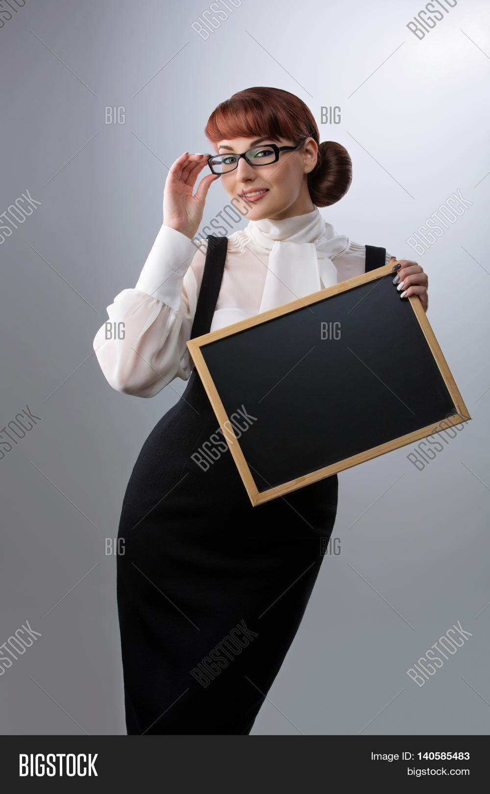 924d6da7d6d2b9 Beautiful young woman in glasses with small blackboard. Teacher wearing  blouse and skirt. Copy