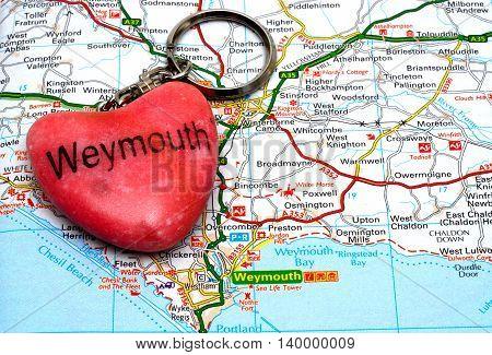 WEYMOUTH, UNITED KINGDOM - JULY 24, 2016 - Pink stone Weymouth keyring on a map Weymouth Dorset England UK Western Europe, July 24, 2016.