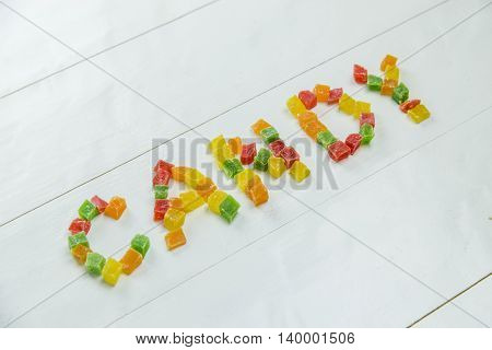 Sweet word with candied fruits on wooden white background